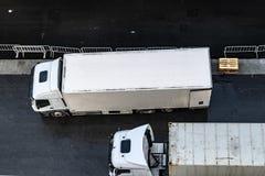 肩并肩在柏油路停放的两辆白色6辆轮车送货卡车空中/顶上的看法  免版税库存图片