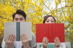 肩并肩坐和读他们的书的年轻愉快的夫妇,面对部分地阻碍,户外春天 免版税库存照片