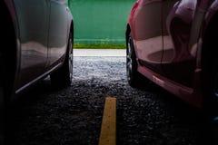 肩并肩站立两辆的汽车 红色和白色汽车 免版税图库摄影