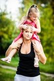 肩扛的母亲和女儿在公园 免版税库存图片