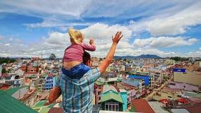 肩膀小女孩的接近的父亲举行屋顶的在城市 股票视频
