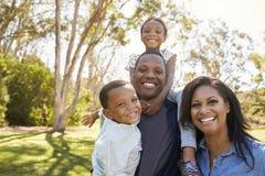 肩膀的家庭运载的孩子,他们在公园走 免版税库存照片