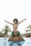 肩膀的父亲运载的儿子在游泳池 图库摄影