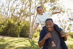 肩膀的父亲运载的儿子,他们在公园走 库存照片
