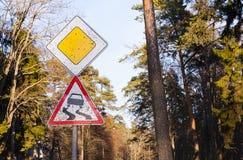 肮脏的交通标志溜滑路在森林里,仔细驾驶在乡下旅行 免版税库存图片