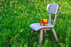 肮脏的儿童的玩具,站立在一把小椅子 库存照片