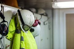 肮脏的垂悬在更衣室的工作者防护服装 库存照片