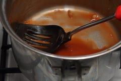 肮脏的平底深锅和开槽的匙子有被烘烤的豆遗骸的,关于 免版税图库摄影