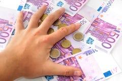 肮脏的手劫掠欧洲钞票和硬币 免版税库存图片