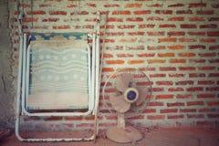 肮脏的折叠的床和电子爱好者的抽象葡萄酒图片与砖砌墙壁在背景中 库存照片