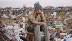 肮脏的无家可归的人坐在垃圾的一个树桩 影视素材