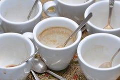 肮脏的杯子和匙子在咖啡以后 免版税图库摄影