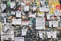 肮脏的海报栏用在俄语的纸通知填装了 免版税库存照片