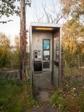 肮脏的现代电话亭没有门不倒空人民 库存照片