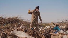 肮脏的男性无家可归的寻找在包裹的转储的生活方式饥饿的人衣物食物与走去看 影视素材