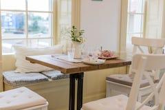 肮脏的空的盘和玻璃在桌上在美丽的咖啡馆 免版税库存图片