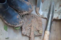 肮脏的胶靴和铁锹在工作以后在庭院里多雨的 免版税库存照片