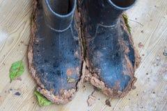 肮脏的胶靴在工作以后在多雨天气的庭院里  图库摄影