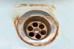 肮脏的落水管滤网、孔与limescale或石灰标度和铁锈对此紧密,肮脏的生锈的卫生间washbowl 库存照片
