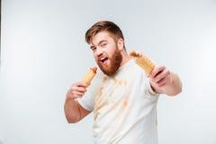 去肮脏的衬衣的饥饿的人吃两根热狗 库存照片