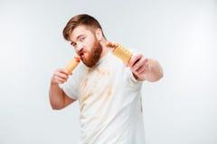肮脏的衬衣的饥饿的有胡子的人吃两根热狗的 免版税库存照片