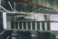 肮脏的金属和具体楼梯在被放弃的大厦,透视 免版税库存照片