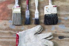 肮脏的难看的东西油漆刷和手套在肮脏的生锈的木ba 免版税库存图片