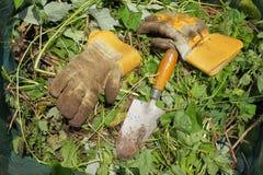 肮脏的从事园艺的手套和修平刀在一个绿色废袋子 库存图片