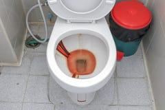 肮脏的洗手间,在公共厕所碗的生锈的水 免版税库存照片