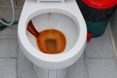 肮脏的洗手间,在公共厕所碗的生锈的水 库存照片