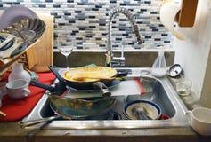 肮脏的水槽在一个杂乱厨房里 免版税库存图片