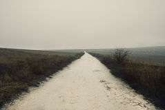 肮脏,有薄雾的乡下公路 库存图片