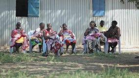 肯尼亚,基苏木- 2017年5月20日:有孩子的妇女从一个地方非洲部落坐椅子 股票录像