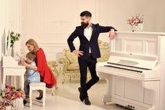 育儿喜悦  家教概念 当母亲教儿子学龄前儿童时,父亲站立近的钢琴,观看 库存照片