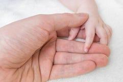 育儿概念 人握他的婴孩的手 免版税库存照片