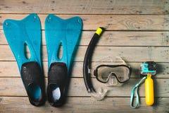 水肺面具、废气管和蓝色鸭脚板与体育摄象机 库存图片