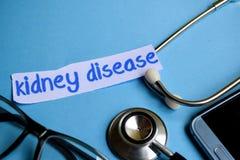 肾病题字有听诊器、镜片和智能手机看法在蓝色背景 免版税图库摄影