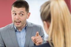 胁迫女性同事的积极的商人在办公室 免版税库存照片