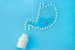 胃由与一些红色和蓝色药片的白色药片做成里面 免版税库存图片