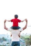 背上产生乘驾儿子的父亲 免版税库存照片