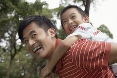 背上享受乘驾的父亲和儿子在公园 免版税库存照片