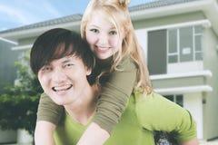 背上使用在他们的房子附近的年轻夫妇 库存照片
