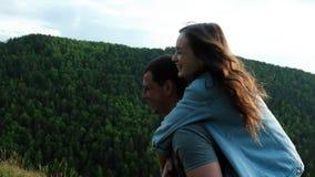 背上给乘驾的愉快的年轻人山的妇女 获得年轻的夫妇乐趣户外 股票录像
