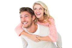 背上给他的女朋友的英俊的人 免版税库存照片