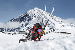 背包、滑雪和杆在背景火山的雪说谎 免版税库存照片
