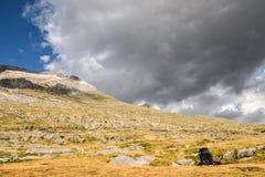 背包和拐杖听任休息在山坡 库存图片