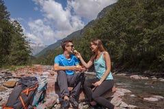 背包徒步旅行者与landjaeger的夫妇在河的午休时间和面包 免版税库存图片