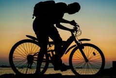 背包徒步旅行者乘驾在海旁边的登山车剪影  图库摄影