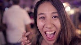 背包徒步旅行者亚裔妇女博客作者旅行的饮用的酒精或啤酒和跳舞与朋友和使用智能手机 股票录像