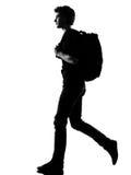 背包徒步旅行者人剪影走的年轻人 免版税库存图片